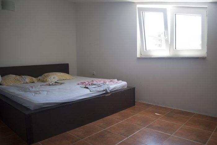 Кровать и окно  в апартаментах villa lazovic