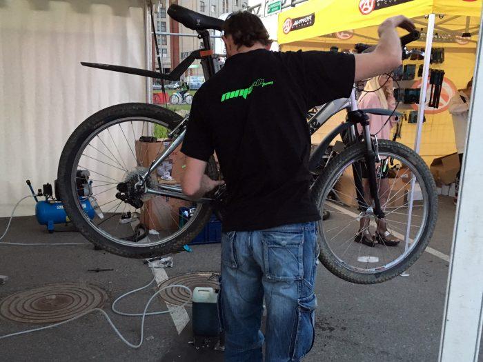 Мастер настраивает новую цепь на велосипеде