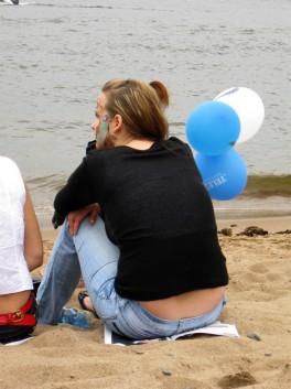 Девушка сидит на журнале Yachts на пляже