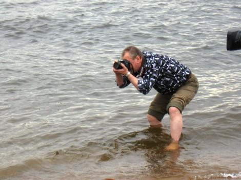 Мужчина снимает регату стоя в поколено в воде